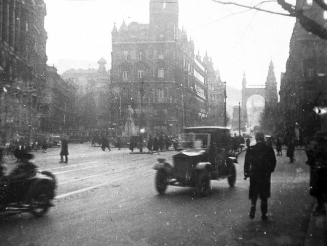 Ferenciek tere, a húszas években még Apponyi térként. Nagy a forgalom, háttérben az Erzsébet híd, a kis fekete autó egy MÁG kistaxi