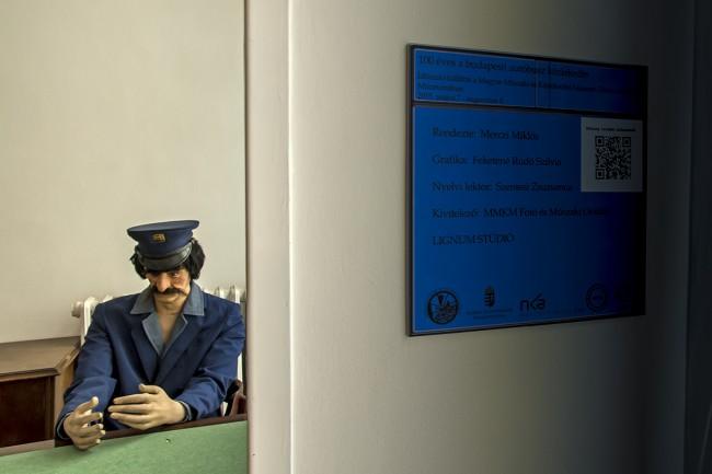 Vélhetően buszsofőrt szerettek volna imitálni a kiállítás hangulatát tükröző arckifejezésű bábuval. Hogy miért ül magában egy asztalnál, láthatóan teljesen értelmetlenül, arról nincs tájékoztatás, csak kiállítás készítőiről...