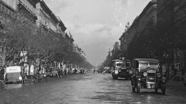 """1924 októberében indították a Lánchídon át Budára közlekedő 3-as járatot, de ez a fotó legalább egy évvel később készült: az Andrássy úton az Oktogonig 1925-ben hosszabbították meg a vonalat. Még """"balra hajts!"""" szabály van érvényben, az út bal oldalán a bécsi Meinl kávét (később csemege áruházlánc) reklámozó furgon előtt Magomobil szürketaxi áll nyitott ajtóval"""