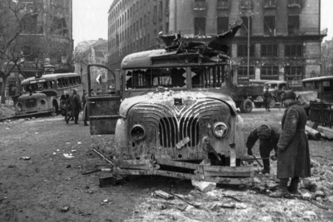 1944-ben, Budapest ostromában súlyosan megsérültek a közlekedési eszközök. Ezeket a már jobboldali közlekedésre alkalmassá tett, 1942-ben a gumihiány miatt vaskerekesítve sínautóbuszként is járatott Mávag N26/36 típusú, Harcsa becenevű buszokat a Deák téren érte utol a végzet, háttérben a későbbi Budapesti Rendőr-főkapitányság (most luxusszálloda) épülete. Új kocsik híján sok ilyen – és ezeknél régebbi - háborús roncsot állítottak helyre, hogy 1945-ben egyáltalán elindulhasson a közösségi közlekedés