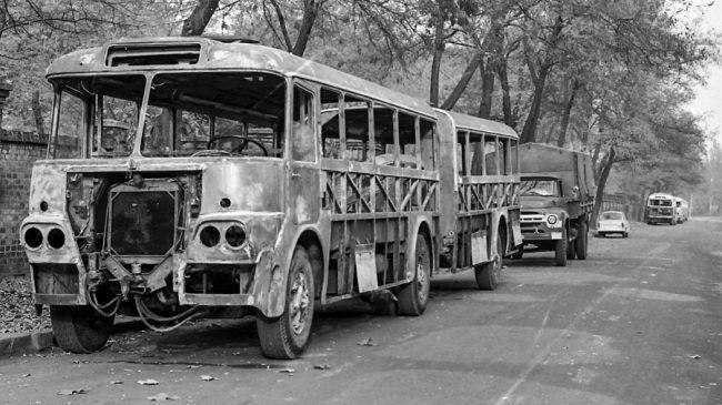 """Duplán érdekes ez a fotó. A Fővárosi Autóbuszüzem tervei alapján ezeket az Ikarus 620/630 típusokat a Mávaut a saját műhelyében házilag csuklósította, két """"félbevágott"""" busz összeépítésével – a képen nem újonnan gyártott busz, hanem főjavításhoz lecsupaszított váz látható. A helyszín a XIII. kerületi Szabolcs utca, de a Dózsa György út túloldalán, az egykori kórház mellett: valószínűleg ezek a javításra váró kocsik (a háttérben Ikarus 66-osok állnak) már nem fértek el a zsúfolt műhely előtt és átvontatták őket"""